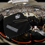 A fisheye lens view of Kelsey Claspell of New London wearing a cap decorated with Jonathan the husky during the School of Business Commencement ceremony at Gampel Pavilion on May 10, 2015. (Peter Morenus/UConn Photo)