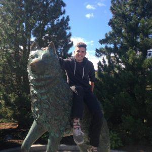 Matthew Brush '16 by the Husky statue.