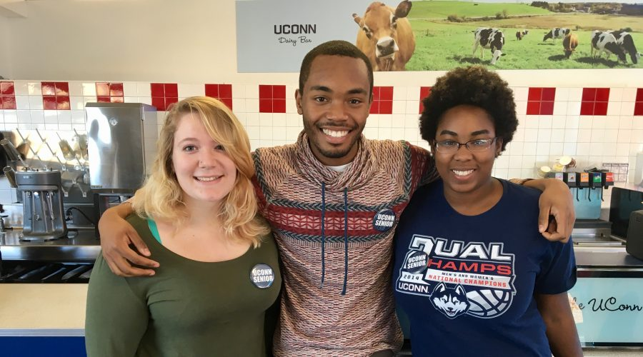 Three seniors wearing senior buttons at the UConn Dairy Bar