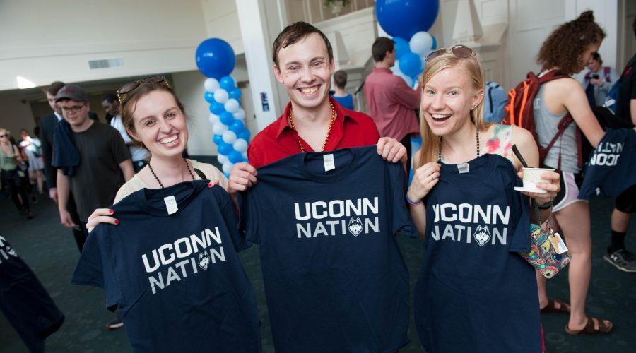 Three seniors smiling while holding UConn Nation t-shirts