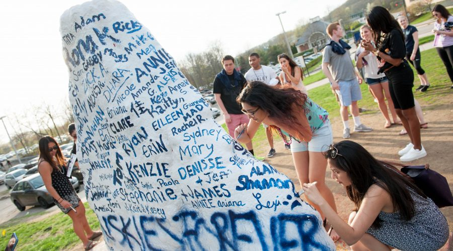 A group of seniors writing their names on the UConn Spirit Rock