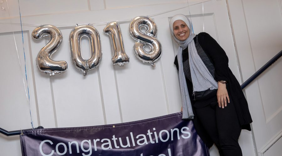 A senior smiling next to a congratulations banner